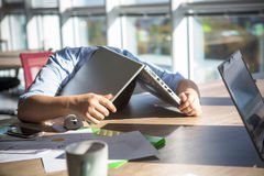 Tired businessman sleeping during his work. Tired businessman sleeping after hard working day in office interior. Man lying on table with laptop computer on Stock Photos
