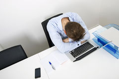 Tired businessman sleeping on laptop at desk in office Stock Photos