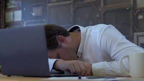 Businessman sleeping on laptop. Tired businessman sleeping on a laptop in small business office for startup team stock video footage