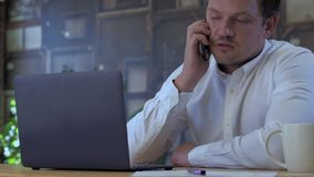 Businessman sleeping on laptop. Tired businessman sleeping on a laptop in small business office for startup team. Waking up by phone call and getting back to stock footage