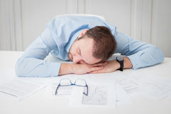 Tired businessman sleeping at the office desk. Businessman tired of overtime work. He is sleeping at the desk surrounded with different paper documents Stock Photo