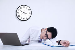 Tired businessman sleeping in the office. Tired businessman sleeping on a laptop with clock in the office Stock Images