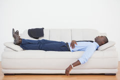 Tired businessman sleeping on the sofa Stock Photography