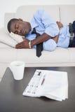 Tired businessman sleeping on the sofa Royalty Free Stock Photos