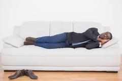 Tired businessman sleeping on sofa Stock Images