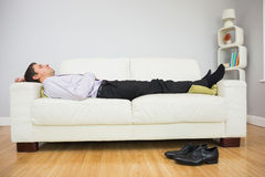 Tired businessman sleeping on sofa in living room Royalty Free Stock Images