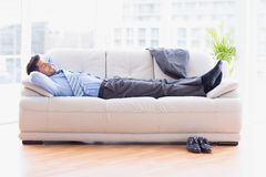 Tired businessman sleeping on a sofa Stock Images