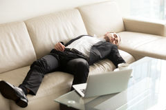 Tired businessman sleeping on sofa in office Stock Photo