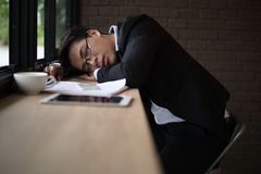 Businessman sleeping on the table at workplace with document, laptop and cup of coffee. Tired businessman sleeping on the table at workplace with document Stock Photos