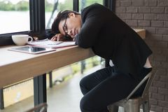 Tired businessman sleeping on the table with document and tablet at coffee shop. stock image