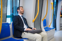 Tired businessman sleeping on the underground metro Stock Photos