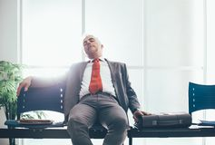 Tired businessman sleeping in the waiting room Stock Images