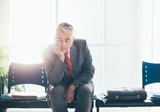 Tired businessman sleeping in the waiting room Stock Image