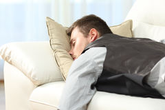 Tired businessman sleeping after work. Tired businessman sleeping lying on a couch after work at home Stock Photo