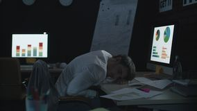 Tired businessman sleeping on work table front computer in dark office. stock footage