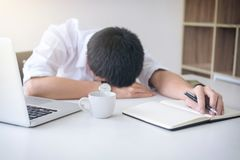 Tired businessman sleeping while working with laptop and writing. Book at work in modern office, people dozing on workplace Royalty Free Stock Photography