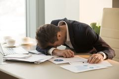 Tired young businessman sleeping on desk in office. Tired businessman sleeping at workplace covered with documents. Overworked frustrated entrepreneur dozing Royalty Free Stock Image