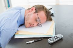 Tired businessman with stack of files on desk Stock Image