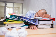 Tired businessman with stack of files on desk Stock Photo