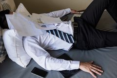 Tired businessman with stack of papers on face. Tired and headache young Asian businessman lying on the bed with pile of working papers covering his face. Hard Stock Photo