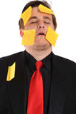 Tired businessman with sticky note paper stock photography