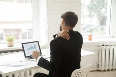 Tired businessman stretching at workplace exhausted after work. Exhausted businessman stretching at workplace in office, tired after long working hours. Male Royalty Free Stock Image