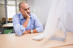 Tired businessman using computer at desk Stock Images