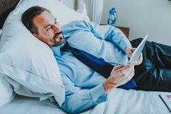 Tired businessman using tablet while relaxing on the bed royalty free stock images