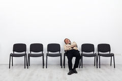 Tired businessman waiting. Sitting on a chairs row Royalty Free Stock Images