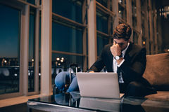 Tired businessman waiting for delayed flight in airport lounge. Young man sitting in waiting room with laptop feeling exhausted Royalty Free Stock Photos