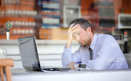 Tired businessman working during coffee break Stock Photography