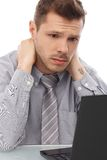Tired businessman working on laptop. Tired, troubled businessman sitting at desk, working on laptop computer Royalty Free Stock Photography
