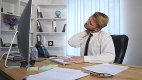 Tired businessman working late at night and loosening his tie in the office stock footage