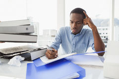 Tired businessman writing notes at desk Royalty Free Stock Image