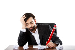Tired businessman writing in the office Stock Images