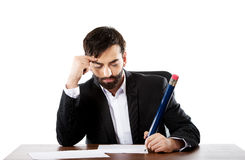 Tired businessman writing in the office Royalty Free Stock Images