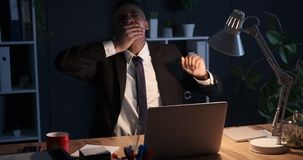 Tired businessman yawning at night office stock footage