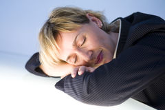 Tired Businesswoman. A metaphorical image of a tired businesswoman sleeping on her desk Royalty Free Stock Image