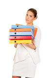 Tired businesswoman carrying heavy binders Royalty Free Stock Images