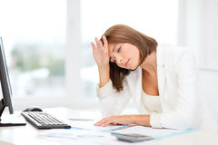 Tired businesswoman with computer and papers. Business, education and technology concept - tired businesswoman with computer, papers and calculator at work Royalty Free Stock Photography