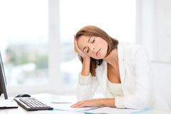 Tired businesswoman with computer and papers Stock Images