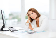 Tired businesswoman with computer and papers. Business, education and technology concept - tired businesswoman with computer, papers and calculator at work Stock Images