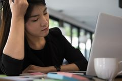 Tired businesswoman with hand on head at office. frustrated youn. G woman with headache at workplace. exhausted female startup in depression after long work Stock Image
