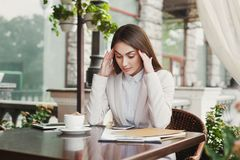 Tired businesswoman outdoors drinking coffee. Tired businesswoman having a headache, sitting at summer terrace cafe. Lifestyle portrait of young business woman Royalty Free Stock Photos