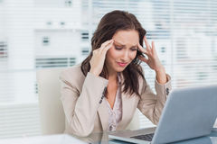 Tired businesswoman having a headache while working on her lapto. P in bright office Royalty Free Stock Photo