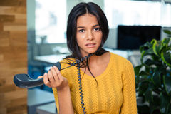 Tired businesswoman holding phone in office Royalty Free Stock Photo