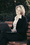 Tired businesswoman with laptop in a city park Royalty Free Stock Photos