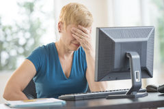 Tired Businesswoman Leaning On Computer Desk Royalty Free Stock Photography