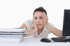 Tired businesswoman leaning on her desk Royalty Free Stock Photography