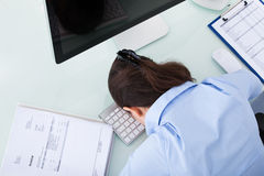 Tired Businesswoman Leaning At Office Desk Stock Photo